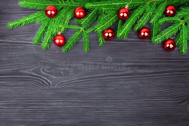 Festlig gräns för jul, dekorativ ram för nytt år, skinande röda bollgarneringar på gröna granfilialer på svart träbakgrund royaltyfria bilder