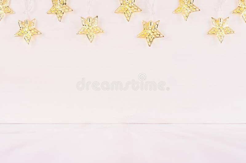 Festlig hem- dekor - guld- stjärnaljus på mjukt vitt wood bräde fotografering för bildbyråer