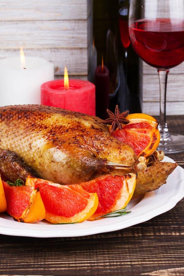 Festlig jul duckar bakat med grapefrukter och rosmarin, exponeringsglas av vin och stearinljus royaltyfri fotografi