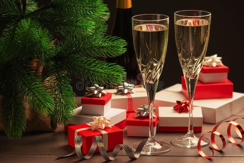 Festlig julafton Två exponeringsglas av champagne, många gåvaaskar med pilbågar och dekorativa band arkivfoto