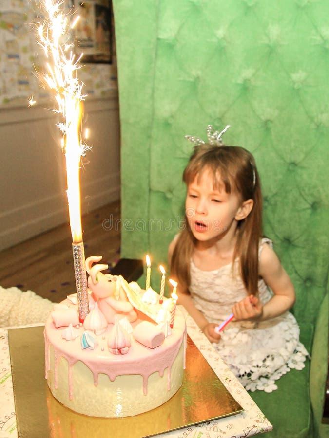 Festlig kaka med ljus på bakgrunden av en årig flicka härliga fyra royaltyfri foto