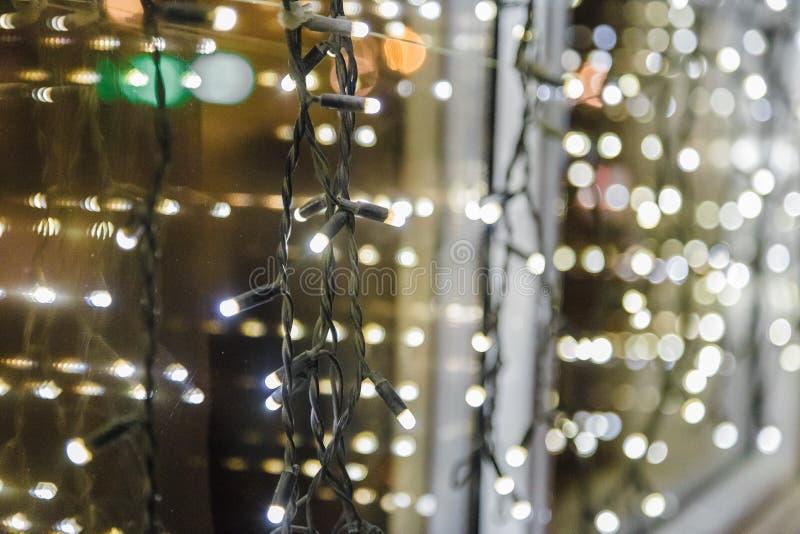 Festlig mörk suddig bakgrund med bokehljus, den elektriska girlanden och huset royaltyfri fotografi