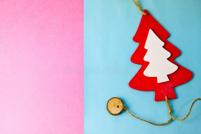 Festlig nytt års jul mång--färgade glade blåa rosa bakgrund med röd en liten leksak träoch vit gullig julgran royaltyfri fotografi