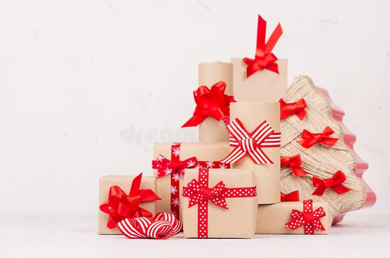 Festlig sammansättning för jul av olika gåvaaskar med röda band och pilbågar runt om julträd på vit träbakgrund fotografering för bildbyråer