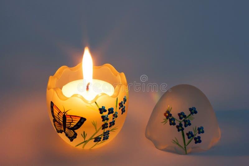 Festlig stearinljus som bränner i en ljusstake som göras av exponeringsglas Festligt målat ägg royaltyfria bilder
