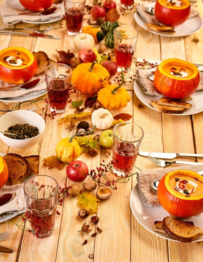 Festlig tabellinställning av pumpasoppa och drinkar royaltyfri bild