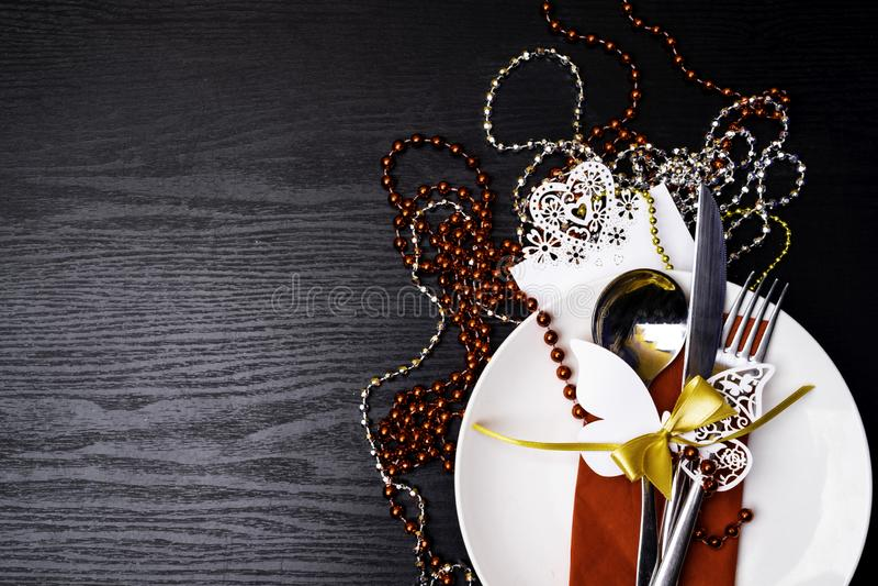 Festlig tabellinställning för jul eller matställe för nytt år: tappninggaffel, sked, kniv på röd servett och julgarneringar på sv arkivbilder