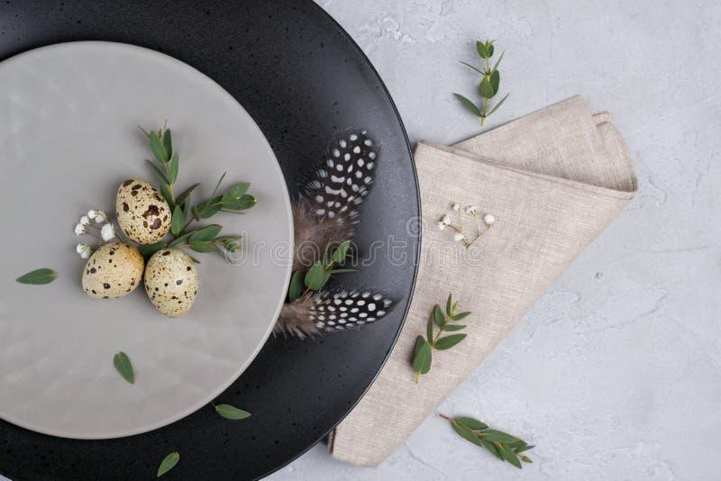 Festlig tabellinställning för påsk med grå färgplattan, kvistar för blad för vaktelägg av eukalyptuns royaltyfri foto