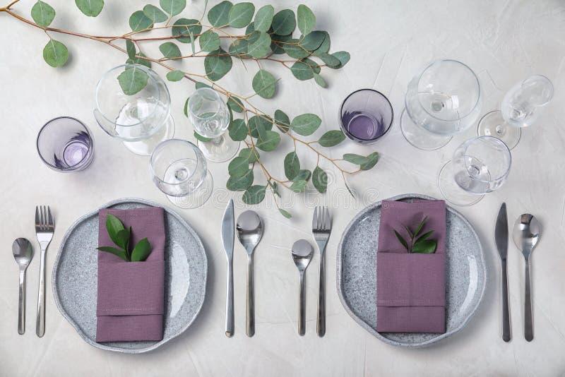 Festlig tabellinställning med plattor, bestick och servetter på ljus bakgrund arkivfoton