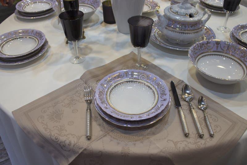 Festlig tabellinställning, purpurfärgad vit uppsättning Vit linnebordduk, purpurfärgat plattabestick Djupa plattaexponeringsglas  royaltyfri foto