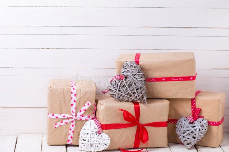 Festliga gåvaaskar och vita dekorativa hjärtor för grå färger och royaltyfria foton