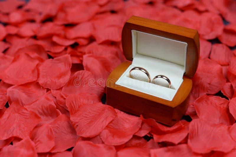 Festliga gifta sig guld- cirklar på gåvaaskar på rosa kronblad med röda blommor arkivfoto