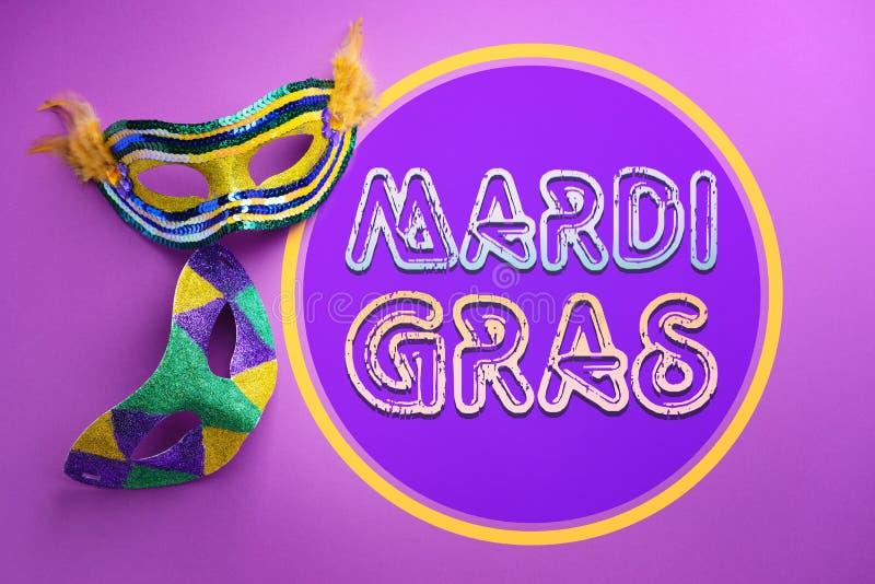 Festliga maskeringar med textMARDI GRAS (också som är bekant som feta tisdag) på färgbakgrund arkivfoton