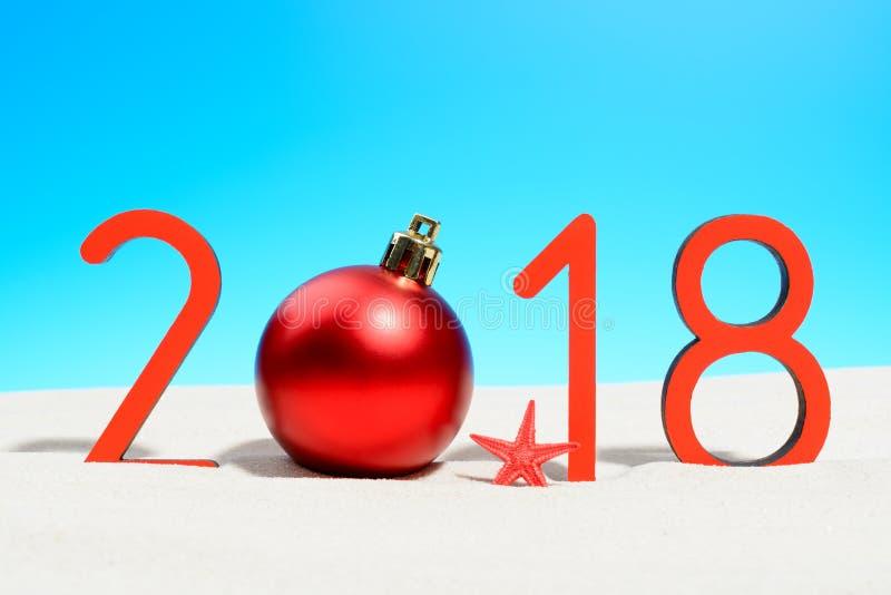 Festliga nya år begrepp med jul klumpa ihop sig en solig tropisk strand med 2018 i röd och kopieringsutrymme på en blå himmel arkivfoto