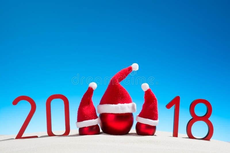 Festliga nya år begrepp med jul klumpa ihop sig en solig tropisk strand med 2018 i röd och kopieringsutrymme på en blå himmel royaltyfria foton