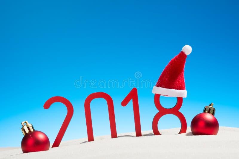Festliga nya år begrepp med jul klumpa ihop sig en solig tropisk strand med 2018 i röd och kopieringsutrymme på en blå himmel royaltyfri fotografi