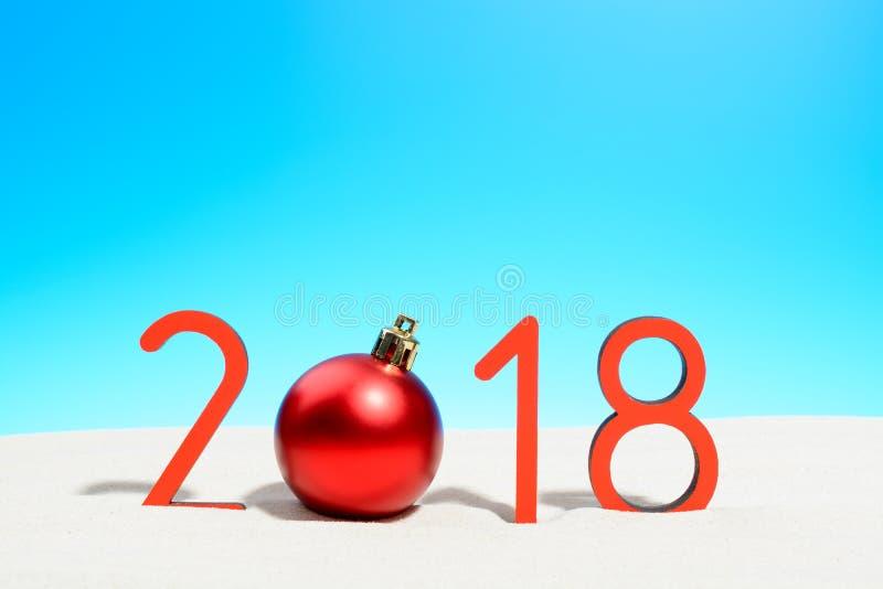 Festliga nya år begrepp med jul klumpa ihop sig en solig tropisk strand med 2018 i röd och kopieringsutrymme på en blå himmel fotografering för bildbyråer