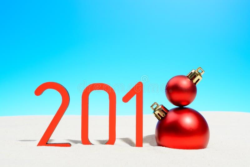 Festliga nya år begrepp med jul klumpa ihop sig en solig tropisk strand med 2018 i röd och kopieringsutrymme på en blå himmel royaltyfria bilder
