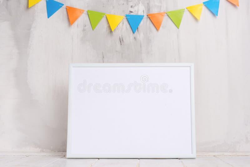 Festligt lynne, barns girland på väggen med den vita tomma ramen för designen av orienteringen Baby shower minimalism arkivbilder