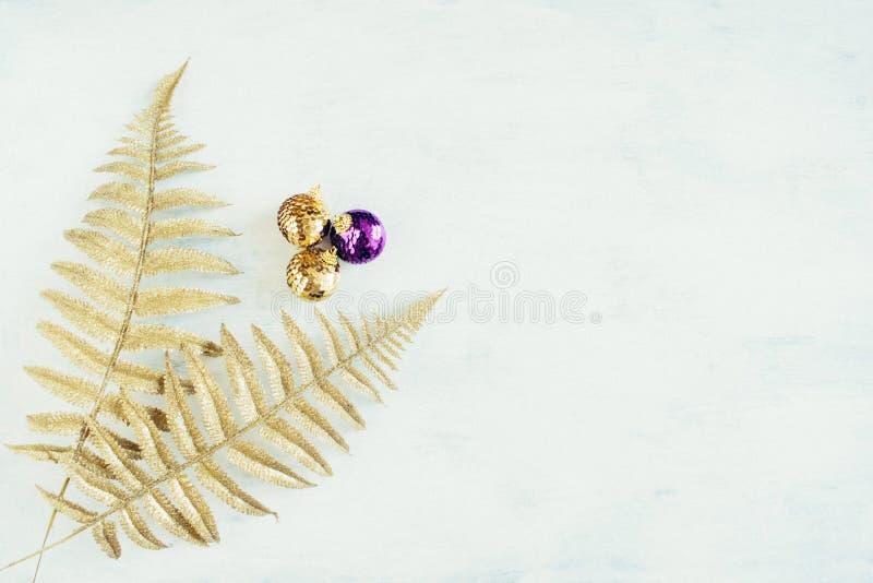 Festligt tema för julferie med den guld- violetta julprydnaden och guld- dekorativa ormbunkesidor arkivfoto