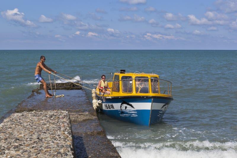 Festmachen des Bootes zu einem konkreten Wellenbrecher für die Einschiffung oder die Ausschiffung von Passagieren vom Strand im E stockfotografie