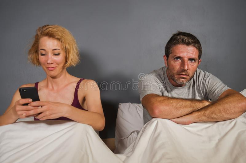Wife using mobile phone in bed with her angry frustrated husband and the man feeling ignored upset and bored in woman internet add. Festyle portrait of stock image