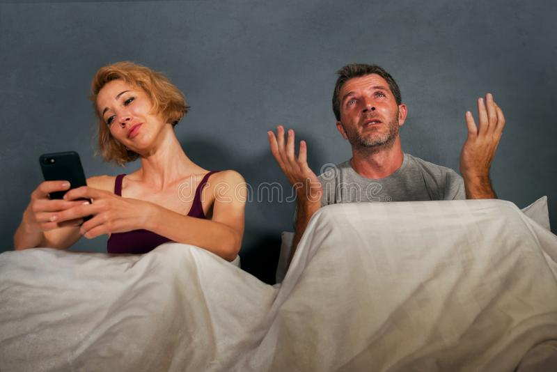 Wife using mobile phone in bed with her angry frustrated husband and the man feeling ignored upset and bored in woman internet add. Festyle portrait of stock photo