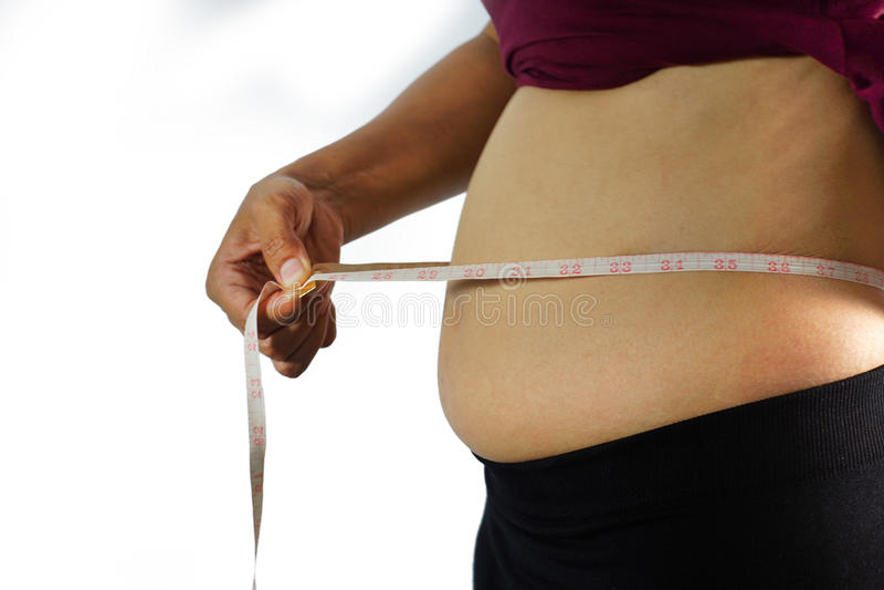 Fet överviktig kvinna som klämmer hennes feta mage isolerad på vit bakgrund, sjukligt fet kvinna, kvinnor med den feta buken arkivbilder