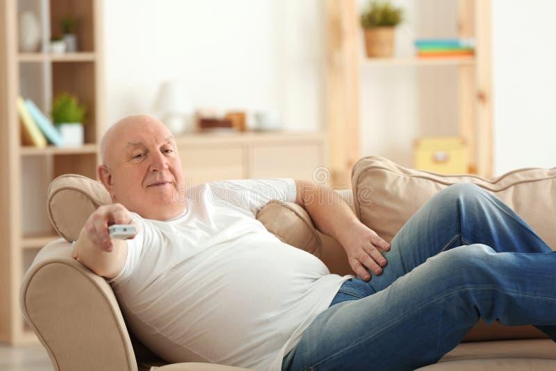 Fet hållande ögonen på TV för hög man, medan ligga på soffan hemma arkivfoto