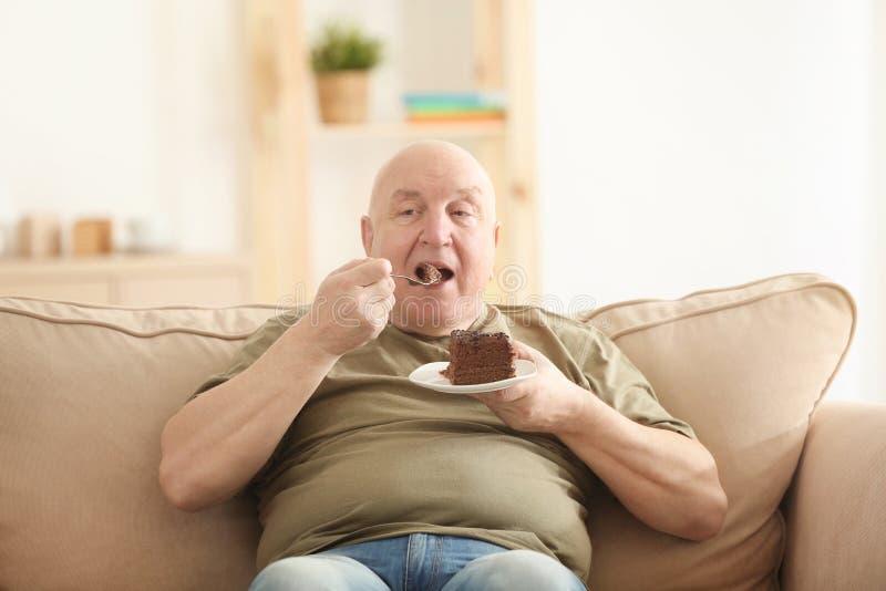 Fet hög man som äter kakan, medan sitta på soffan hemma royaltyfri bild
