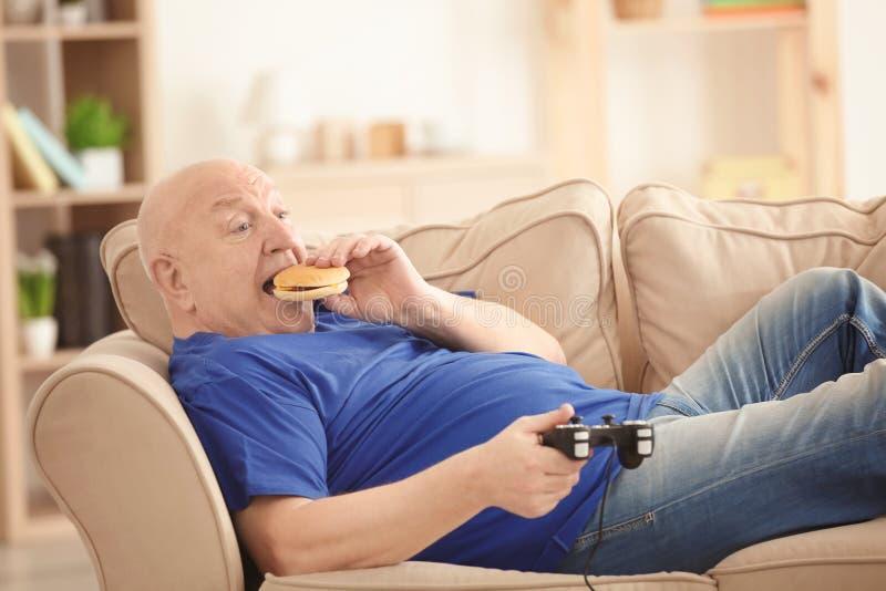 Fet hög man som spelar videogamen och äter hamburgaren, medan ligga på soffan hemma royaltyfri bild