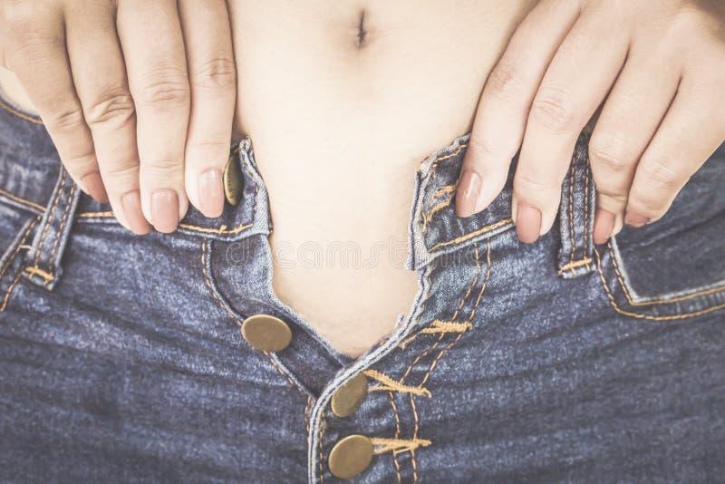 Fet kvinna med den stora buken som försöker att bära åtsittande jeans arkivfoto