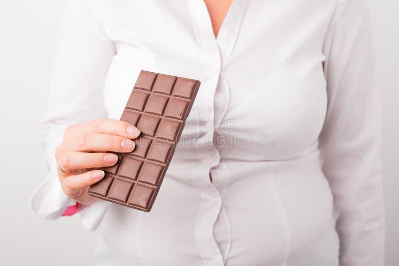 Fet kvinna som äter choklad royaltyfria foton