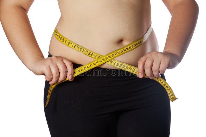 Fet kvinna som mäter hennes midja med ett gult mäta band Förminskning av övervikt- och fetmabehandling fotografering för bildbyråer