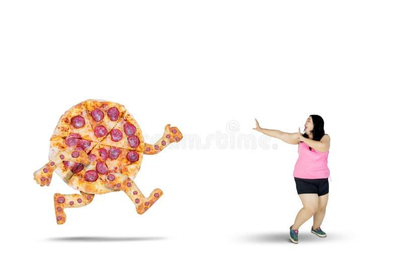 Fet kvinnaspring i väg från en pizza royaltyfria bilder