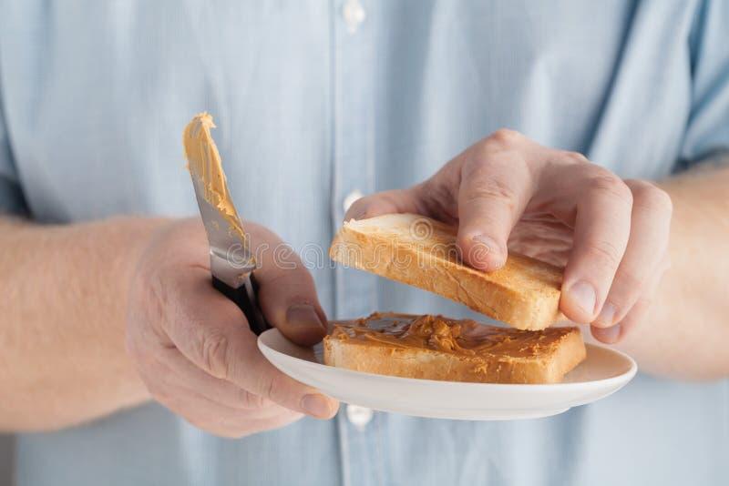 Fet man att äta den typiska hög-kalori frukosten med rostat bröd- och jordnötsmör royaltyfria foton