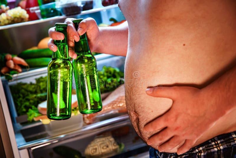 Fet man med ett öl i hans hand bredvid kylen arkivfoto