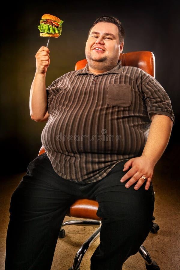Fet man som äter snabbmathamberger Frukost för överviktig person royaltyfri foto