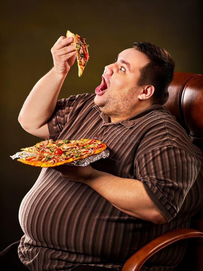 Fet man som äter snabbmatskivapizza Frukost för överviktig person royaltyfri bild