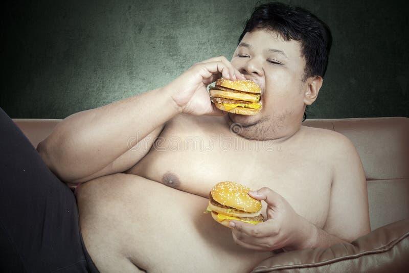 Fet man som äter två hamburgare royaltyfri fotografi
