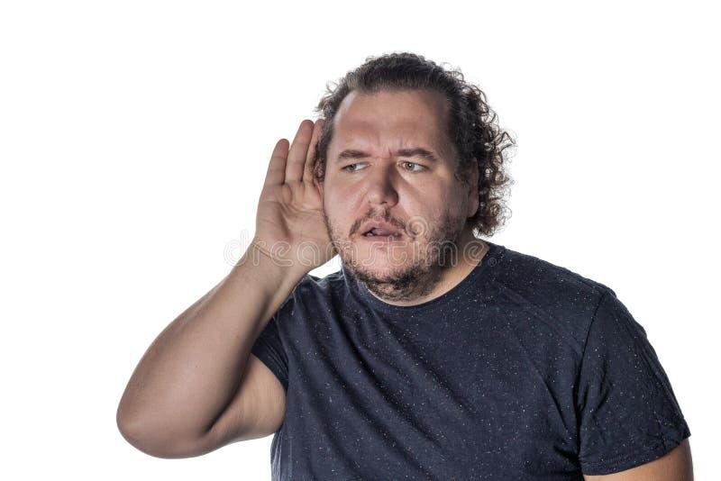 Fet man som bär en tillfällig dräkt som försöker att höra någon sätta hans hand på hans öra som står på en vit bakgrund arkivbild