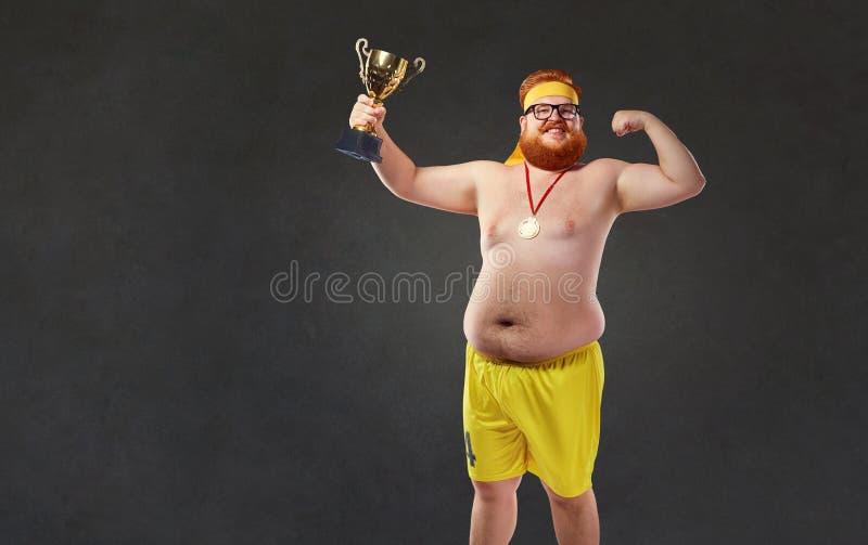 Fet naken man med en kopp för mästare` s i hans händer arkivfoton
