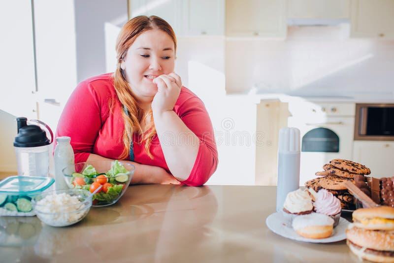 Fet ung kvinna i köksammanträde och ätamat Se sött skräpmål på vänster sida frestelse Sund mat p? fotografering för bildbyråer