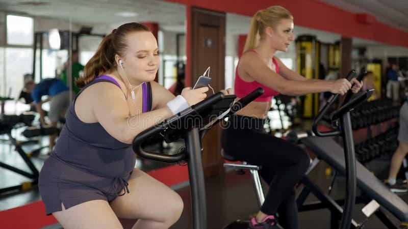 Fet ung kvinna som använder konditionmobilen app, medan utbilda för att förlora vikt i idrottshall fotografering för bildbyråer