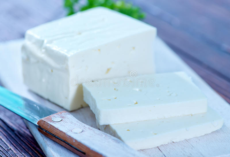 Feta cheese. On board and on a table stock photo