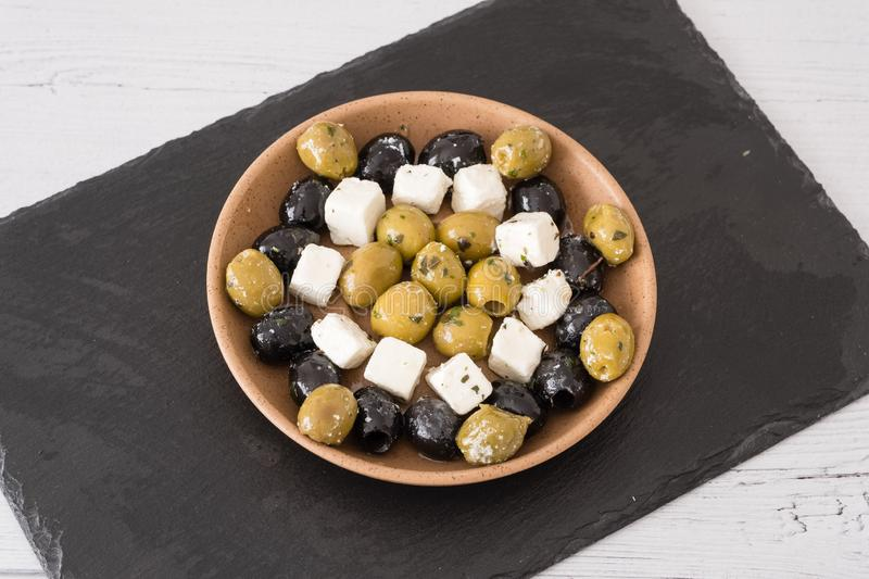 Feta Cheese with Green and Black Olives served in a Bowl. A preparation of green and black olives served in a bowl with small squares of feta cheese with some stock image