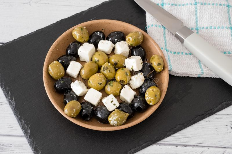 Feta Cheese with Green and Black Olives served in a Bowl. A preparation of green and black olives served in a bowl with small squares of feta cheese with some stock photo