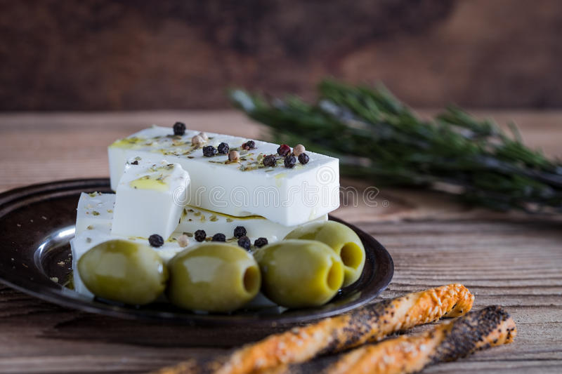 Feta cheese with green olives and fresh bread sticks stock photos