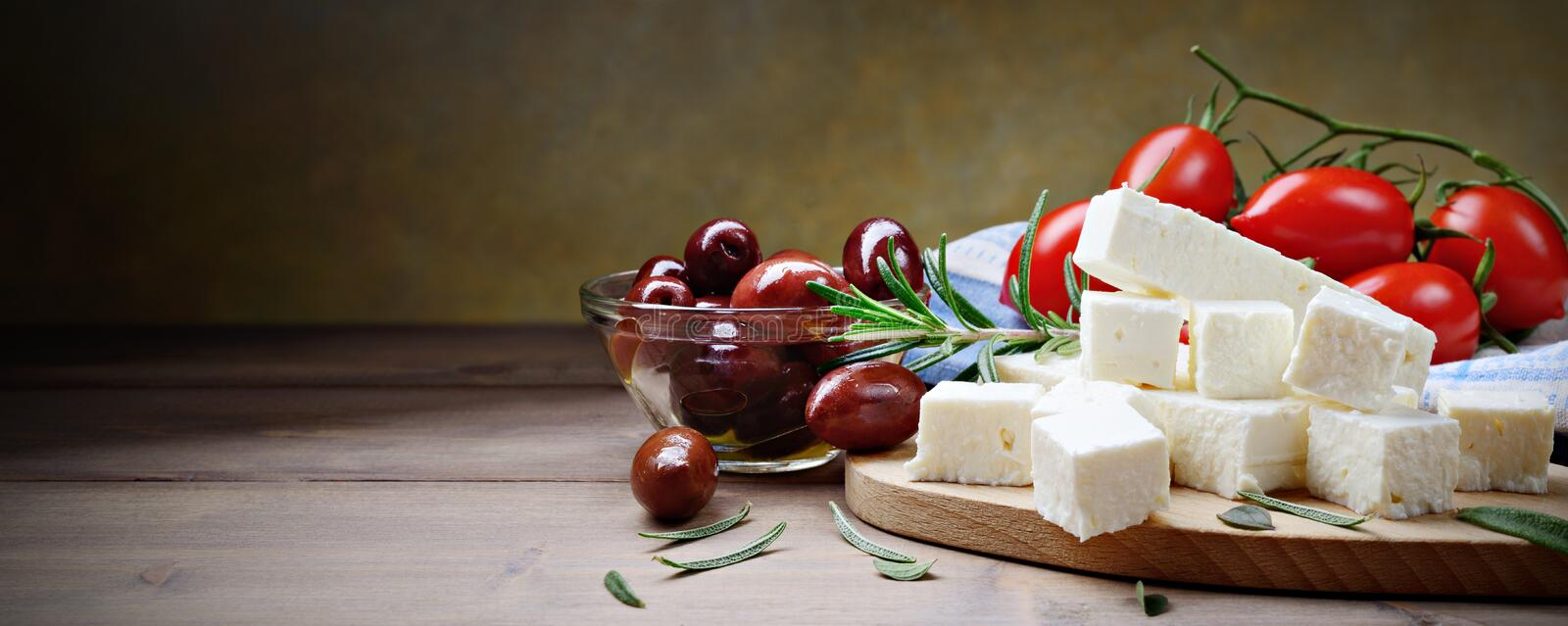 Feta cheese with kalamata olives, tomatoes and rosemary on a wooden background with space for text. Feta and kalamata olives two famous Greek products here royalty free stock photos