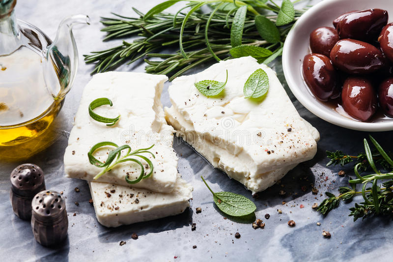 Feta cheese with olives and green herbs. On gray marble background stock photography